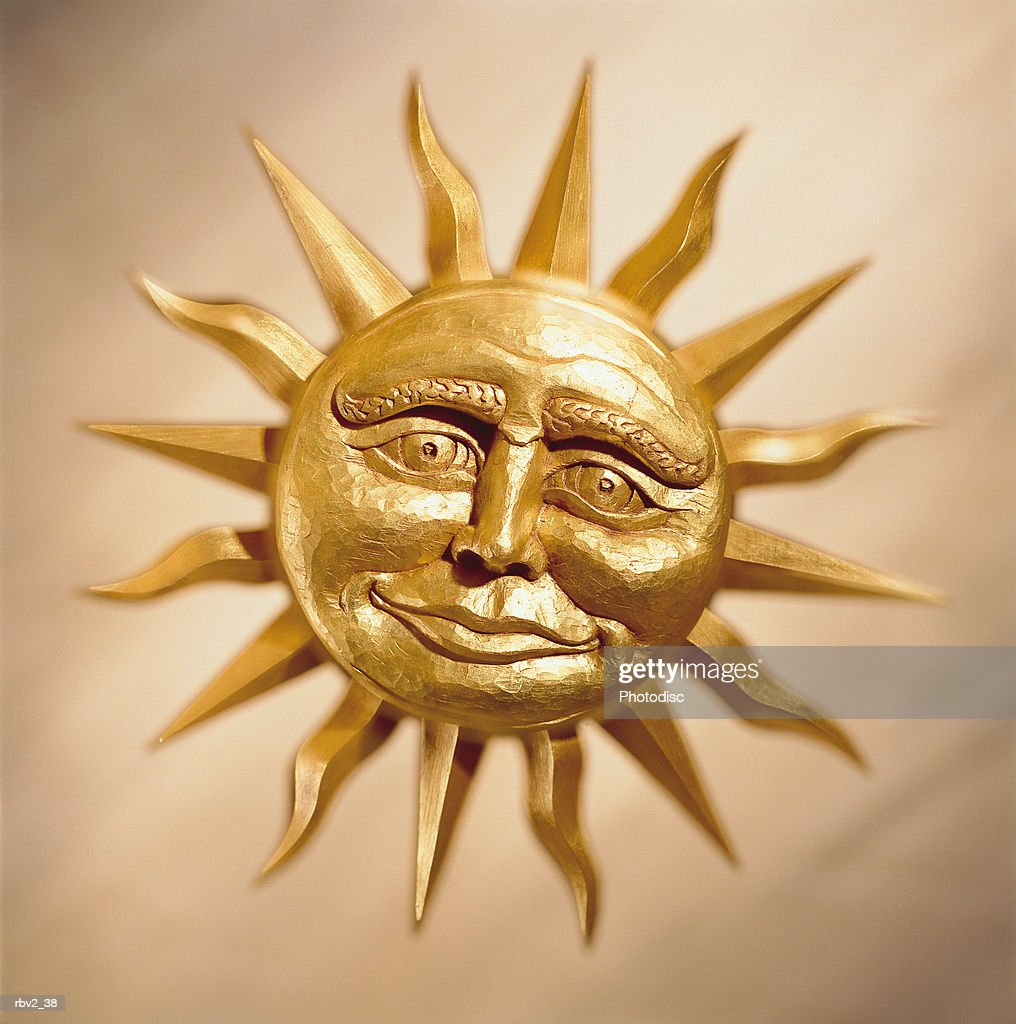 a smiling bronze cast sun rests on a cream background : Foto de stock