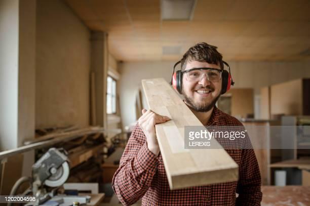a smiling carpenter carries a beam of work - schreiner stock-fotos und bilder