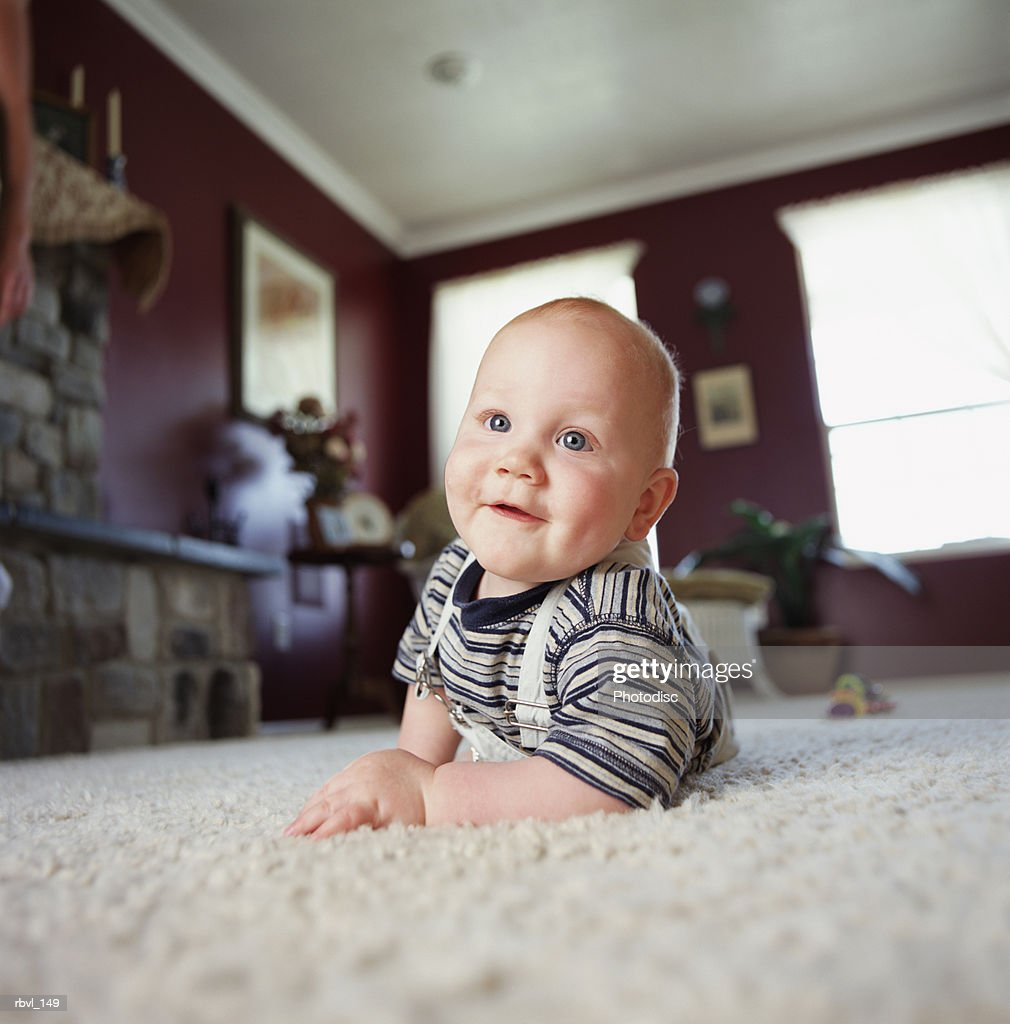 a smiling caucasian baby boy is crawling on a white carpet and smiling at the camera : Stockfoto