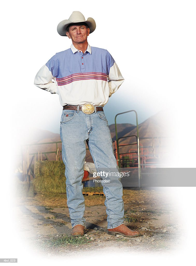 a smiling caucasian cowboy in jeans wearing boots and a white cowboy hat is standing with his hands behind his back with a livestock pen behind him : Foto de stock