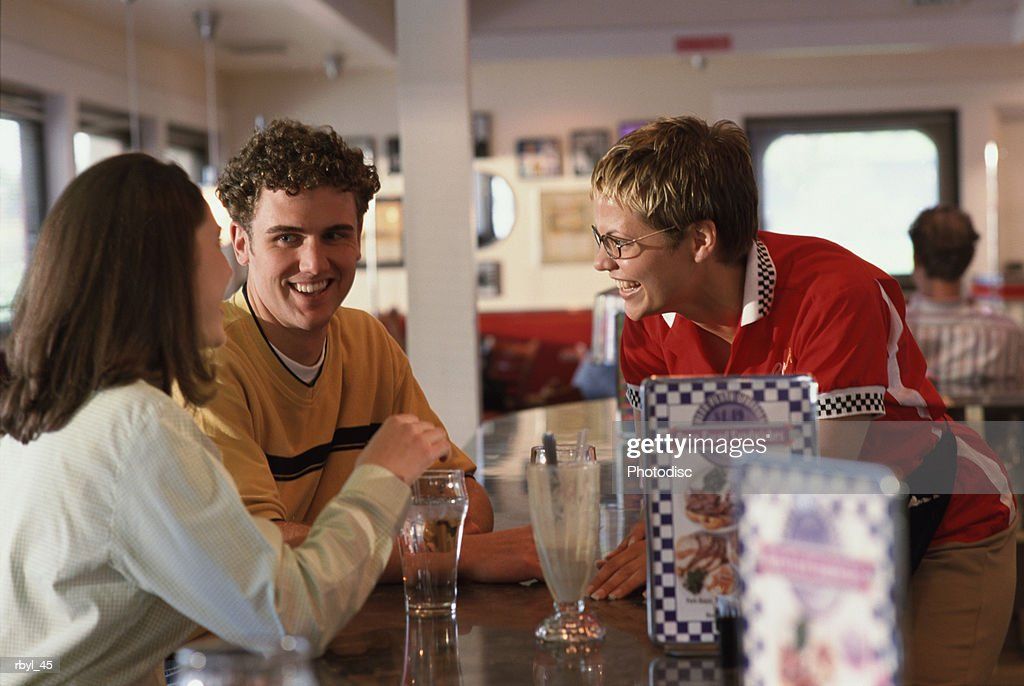 a smiling young couple are sitting at the counter of a cafe or diner and talking a short haired laughing waitress : Foto de stock