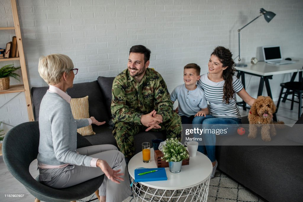 a soldier and his family at a psychotherapist during a session : Stock Photo