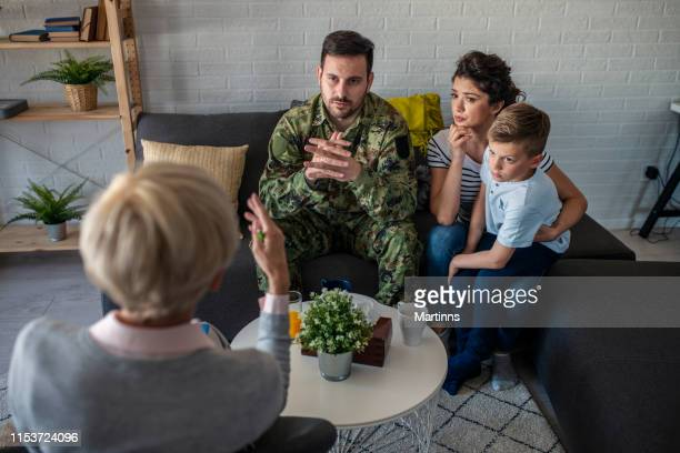 a soldier and his family at a psychotherapist during a session - military doctor stock photos and pictures