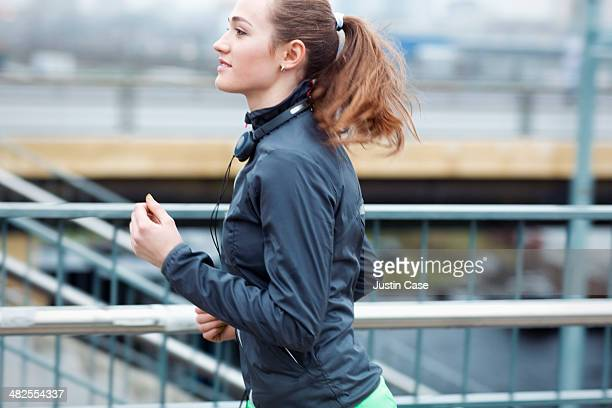 a sporty young smily woman runs in the city
