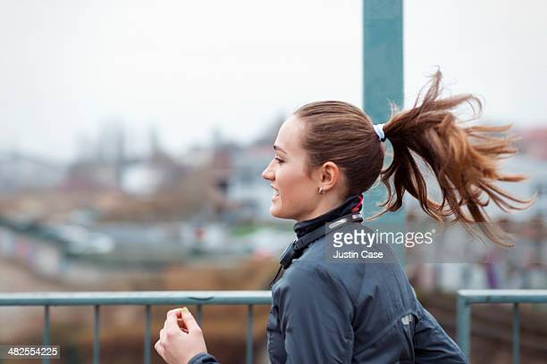 a sporty young woman runs through the city - joggeuse photos et images de collection