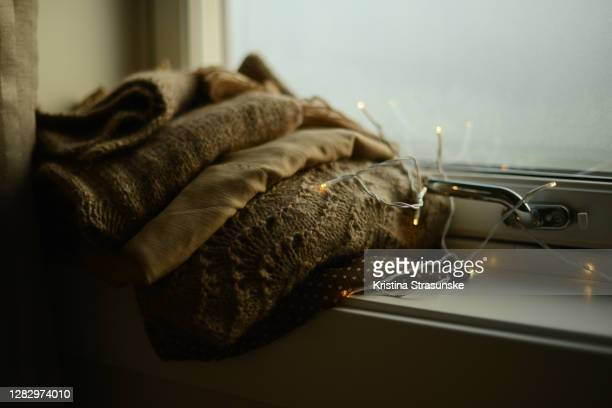 a stack of knitted sweaters and silk blouses in matching color in a windowsill by a light chain - kristina strasunske stock pictures, royalty-free photos & images