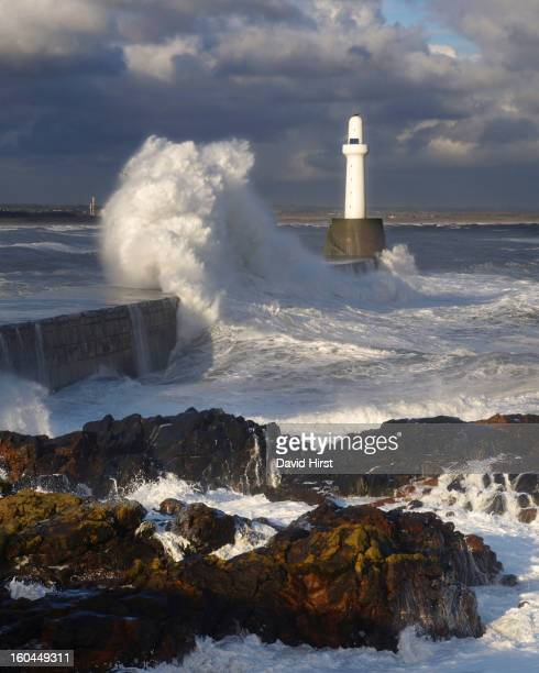 A stormy north sea wave crashes against the southern breakwater of Aberdeen harbour entrance on the east coast of Scotland in Aberdeenshire. Sharp...