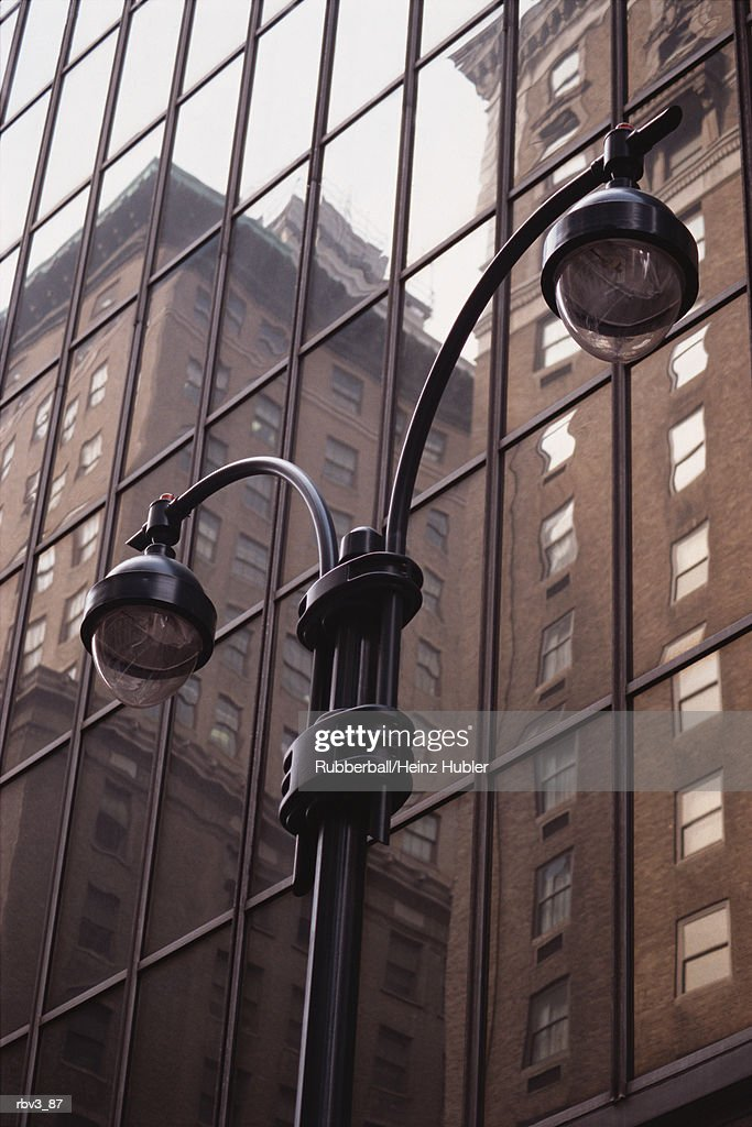 a street lamp stands in front of windows reflecting brown skyscrapers : Foto de stock