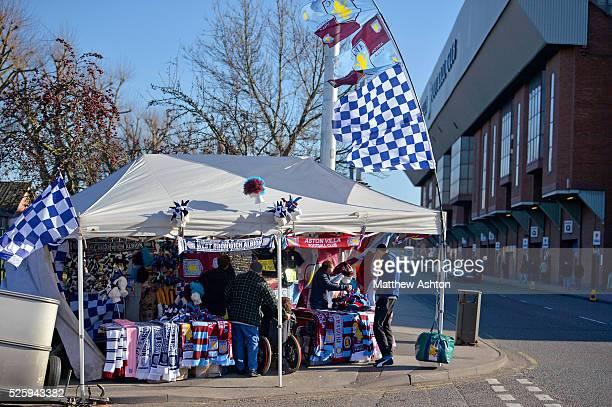 a street seller sells West Bromwich Albion Aston Villa scarves and badges outside of the Aston Villa ground