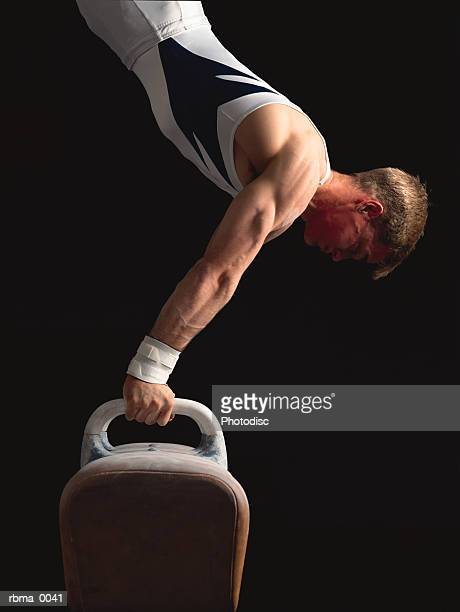 a strong male gymnast does a handstand on the pommel horse