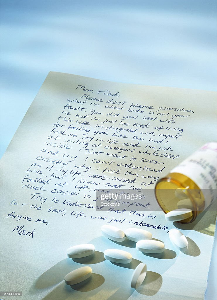 a suicide note with an open vial of medical pills : Stock Photo