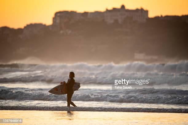 un surfista sosteniendo su tabla saliendo del agua de la playa de somo. - cantabria fotografías e imágenes de stock