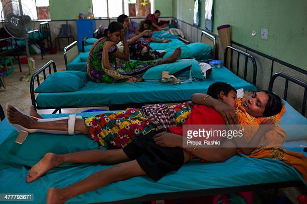 a survivor of the Rana Plaza building collapse rests on a hospital bed with her child in Savar During the incident she was working on the 3rd floor...