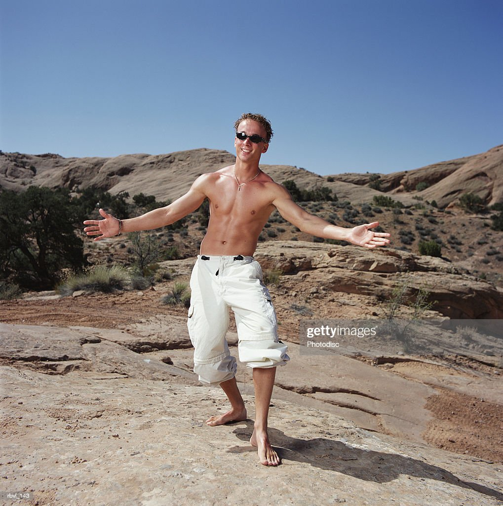 a tan caucasian young man in sunglasses is wearing baggy white pants and no shirt as he stands gesturing with outstretched arms toward the camera : Foto de stock