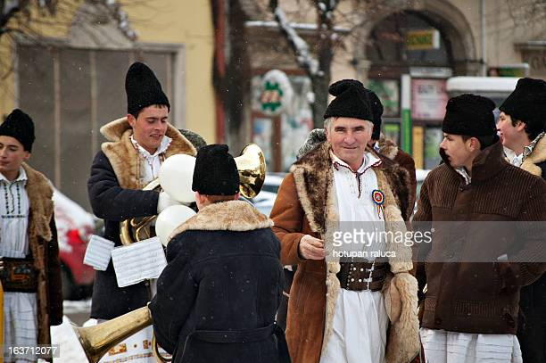 CONTENT] a teacher and his students wearing traditional romanian costumes after performing at an outdoor traditional carols concert in unirii square...