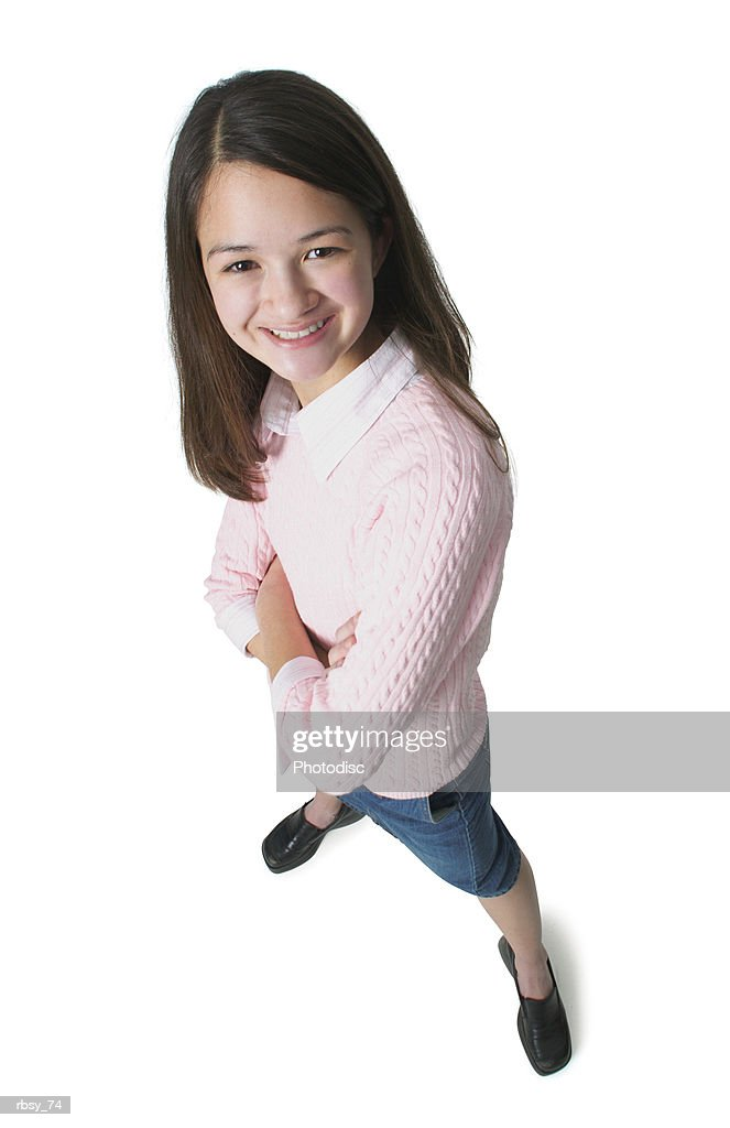 a teenage asian girl in a jean skirt and pink sweater folds her arms and smiles up at the camera : Foto de stock