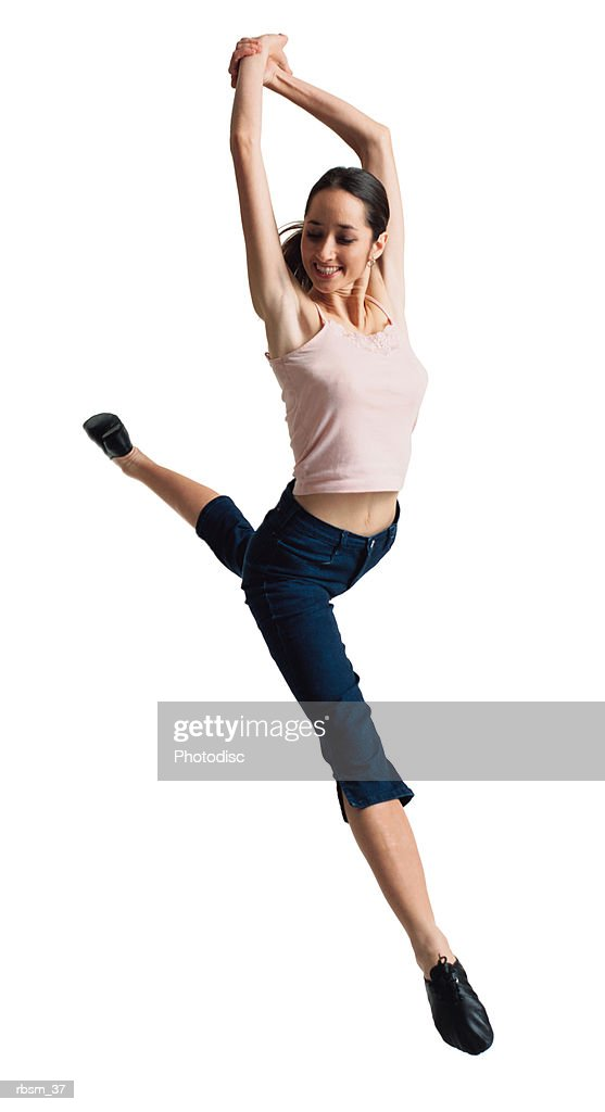 a teenage caucasian female dancer in jeans and a pink tank top jumps through the air while raising her arms and clasping her hands together : Foto de stock