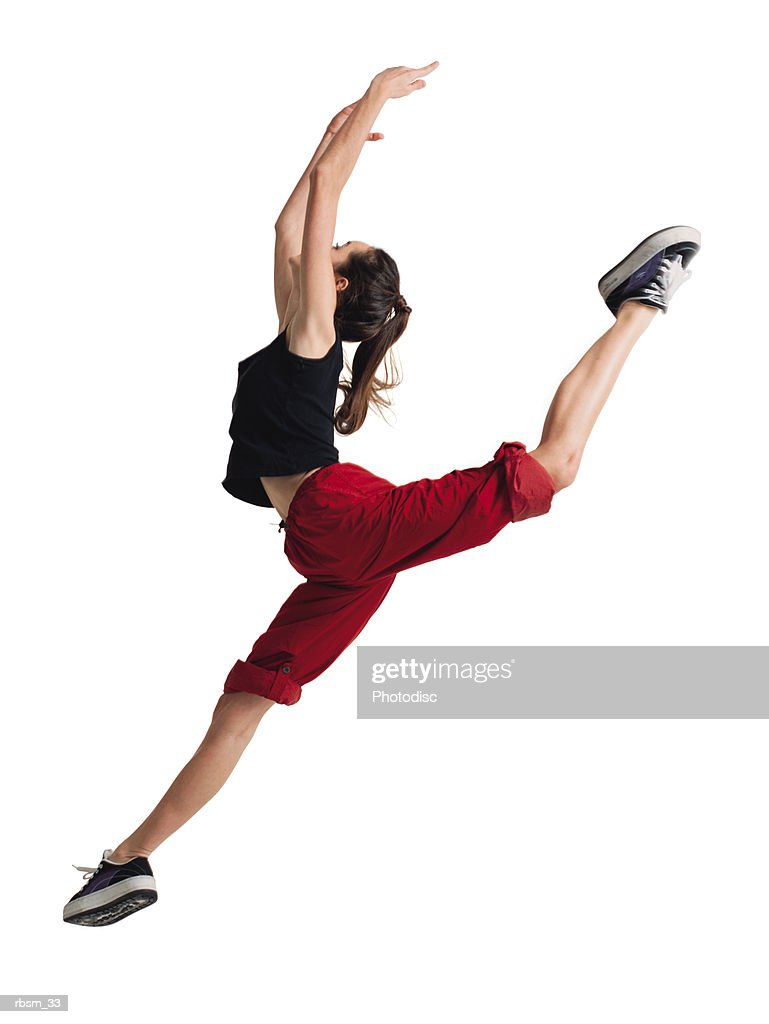 a teenage caucasian female dancer in red pants and a black tank top jumps forward raising her arms and throwing her leg back : Foto de stock