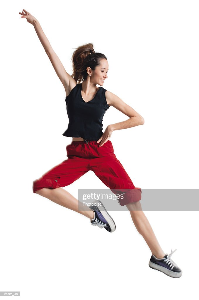 a teenage caucasian female dancer in red pants and a black tank top jumps up and to the side while raising one arm : Foto de stock