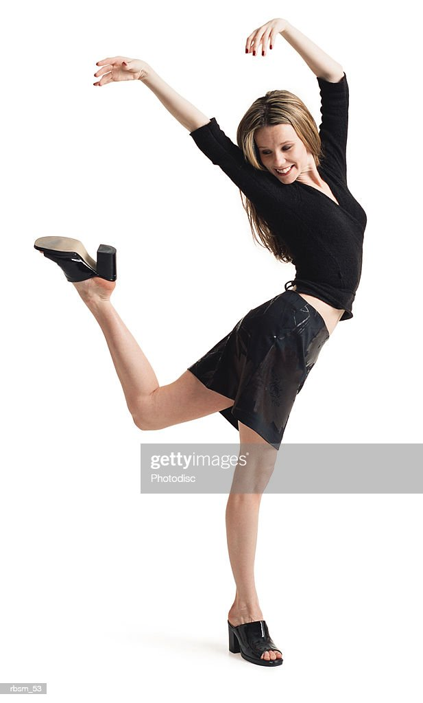 a teenage caucasian female in a black skirt and shirt balances on one leg as she playfully throws her arms up into the air : Foto de stock