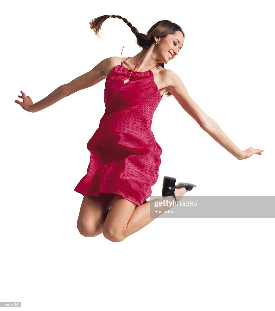 a teenage caucasian female in a pink sun dress and braids jumps up into the air and pulls her feet up underneath her : Foto de stock