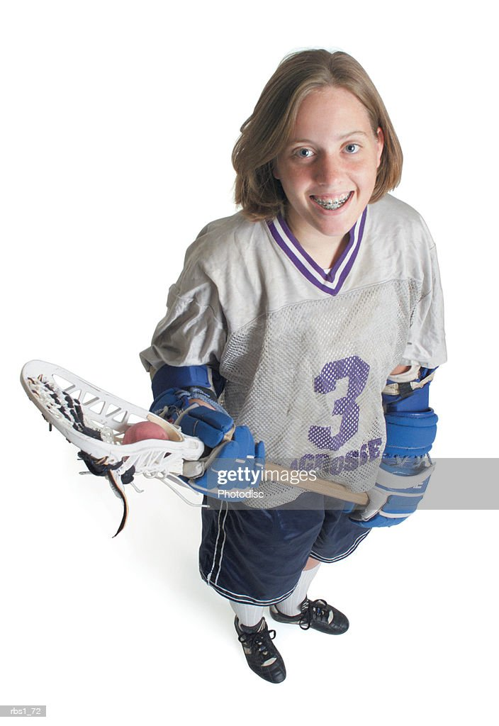 a teenage caucasian female in a white jersey holds her lacrosse racket and smiles as she looks up into the camera : Foto de stock
