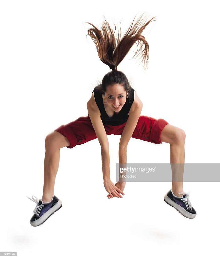 a teenage caucasian female in red pants and a black tank top plays leap frog by jumping up while bending over : Foto de stock