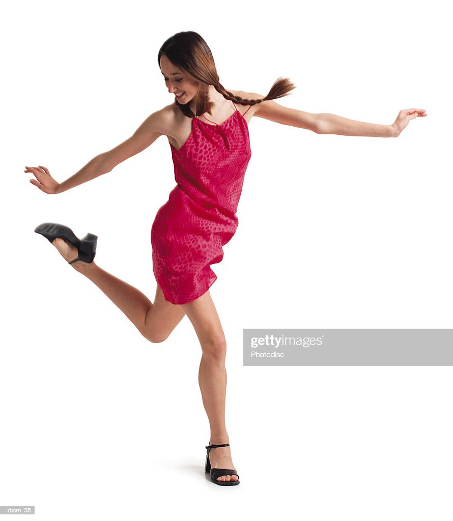 a teenage caucasian female with braids in a pink sun dress walks and jumps forward while spreading her arms out : Foto de stock