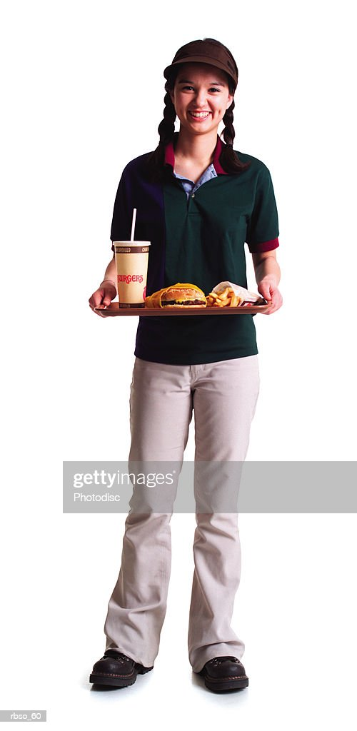 a teenage caucasian girl in a fast food uniform serves a burger and fries on a tray : Foto de stock