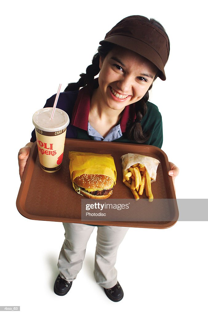 a teenage caucasian girl in a fast food uniform serves a burger and fries as she smiles and looks up at the camera : Foto de stock
