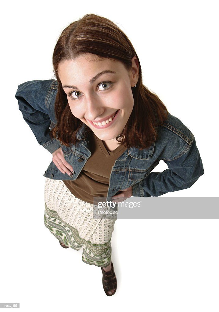 a teenage caucasian girl in a skirt and jean jacket puts her hands on her hips as she smiles up at the camera : Foto de stock