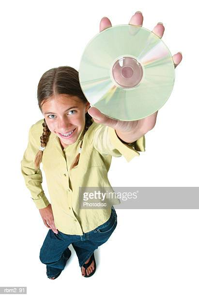 a teenage caucasian girl in jeans and a green shirt holds up a cd as she smiles up into the camera - girls flashing camera stock pictures, royalty-free photos & images