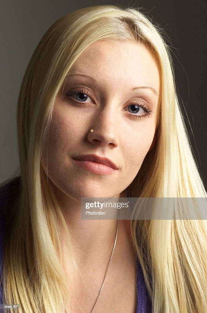 a teenage caucasian girl with long straight blond hair has a pierced nose and an expression of calm : Stockfoto