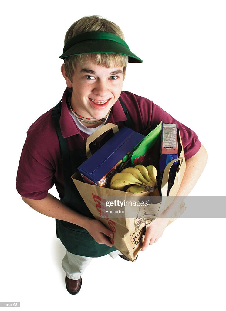 a teenage caucasian male grocery store bagger carries a bag of groceries and looks up at the camera : Foto de stock