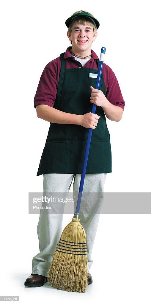 a teenage caucasian male grocery store employee stands with a broom : Foto de stock