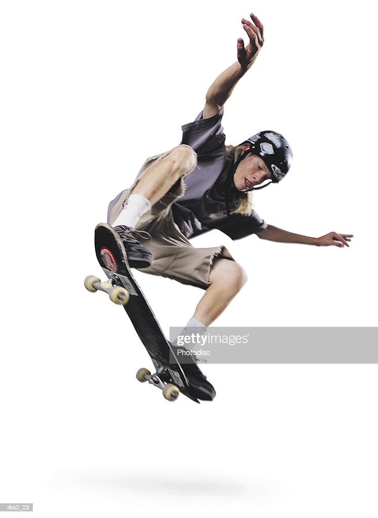 a teenage caucasian male jumps up in the air on his skateboard while raising his hands up in the air : Foto de stock