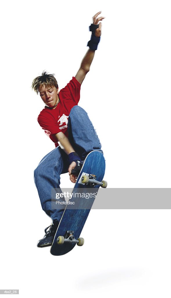 a teenage caucasian male skateboarder in a red shirt and blue jeans jumps his board while raising his arm up high : Foto de stock