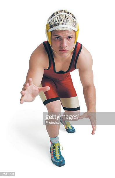 a teenage caucasian male wrestler in a red uniform stands ready to pounce - レスリング ストックフォトと画像
