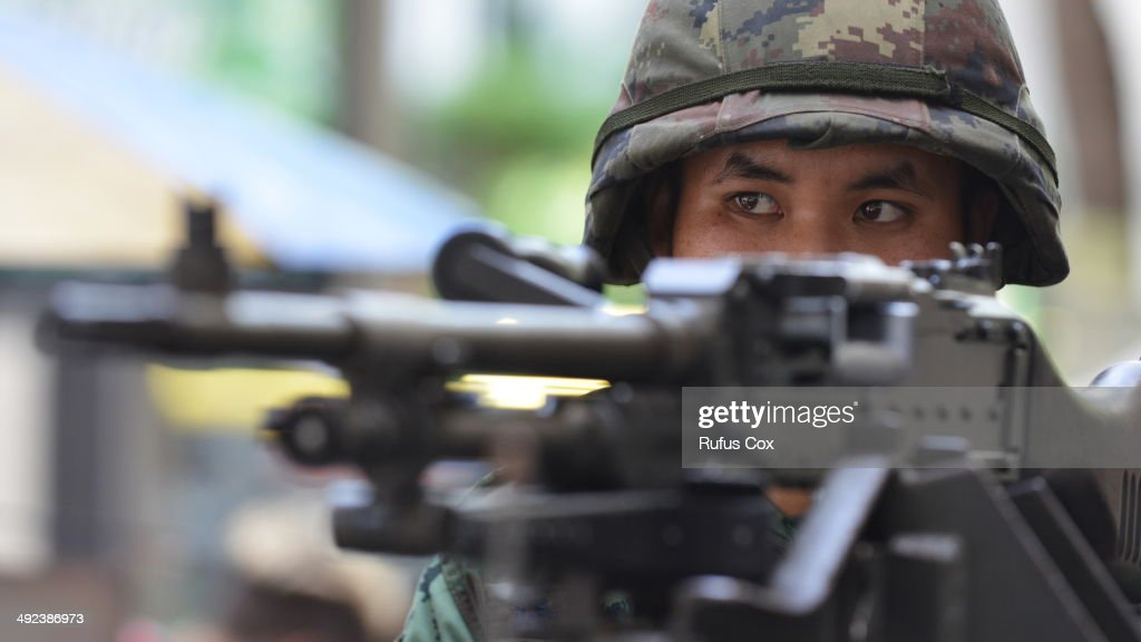 a Thai army soldier stands guard on a city centre street after martial law was declared on May 20, 2014 in Bangkok, Thailand. The army imposed martial law across Thailand amid a deepening political crisis that has seen six months of protests and claimed at least 28 lives.