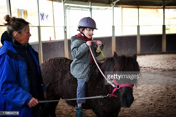EQUISENS a therapeutic riding center in AsnierelesDijon France Hippotherapy session with a child having autistic disorders and psychomotor delay