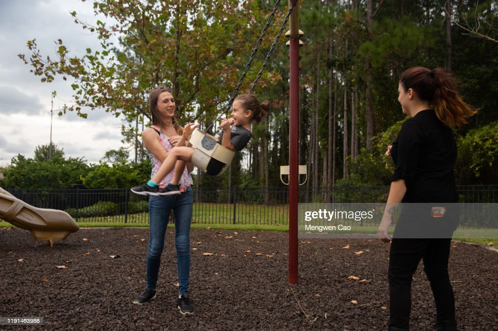 a trans woman playing with her daughter and wife on the playground : Stock Photo