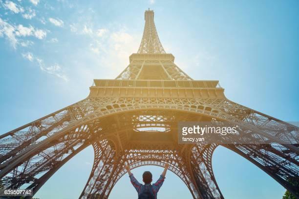 a traveler raising arms under the Eiffel Tower in Paris