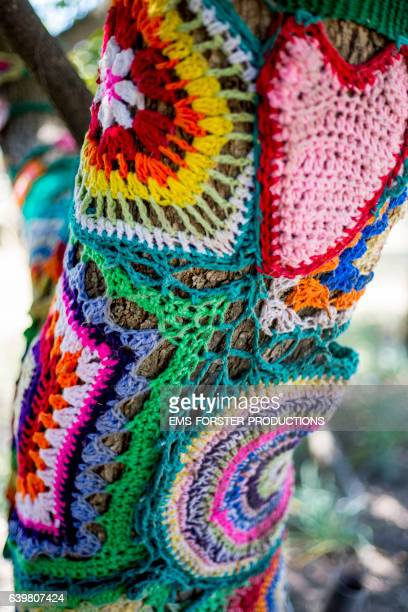 a tree trunk is decorated with colorful crocheted design - creation - ems forster productions stock pictures, royalty-free photos & images