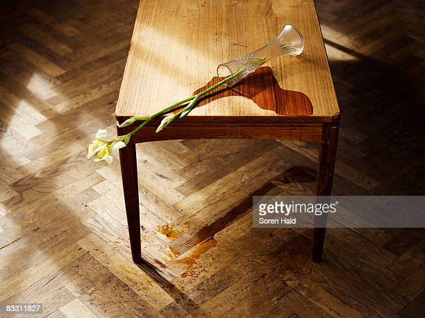 a vase knocked over on a table with spilled water