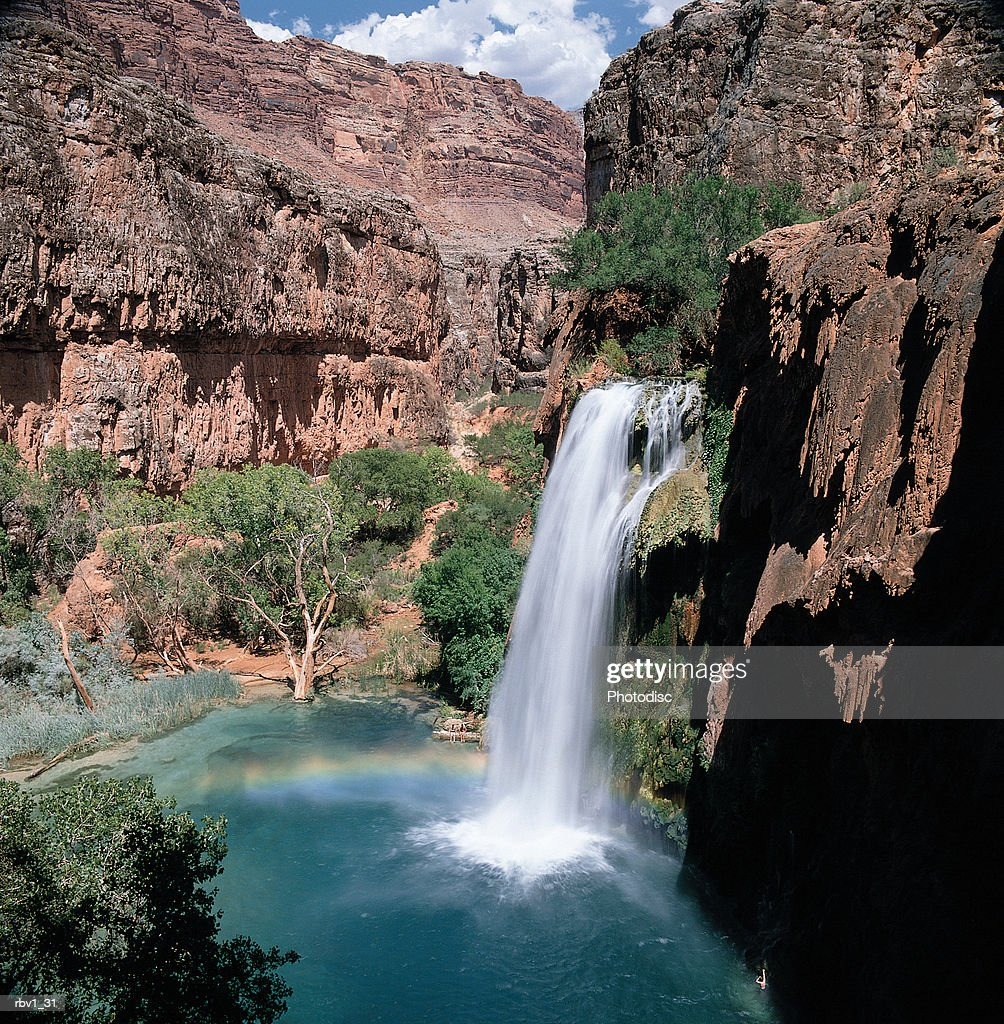 a waterfall falls into blue-green water amongst green trees and jagged mountain cliffs under a blue sky with clouds : Stock Photo