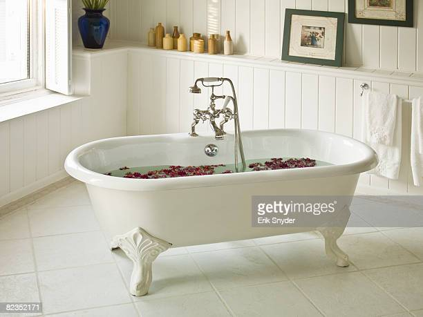 a water-filled bathtub with flower petals