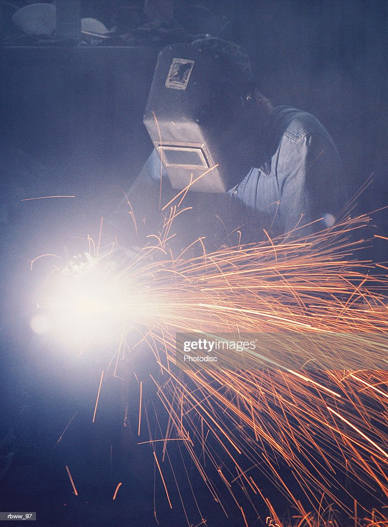 a welder wearing  protective eyewear works on metal while sparks fly : Foto de stock