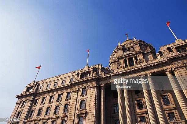 a western-styled building with several pillars under a blue sky, low angle view, shanghai, china - low angle view photos et images de collection