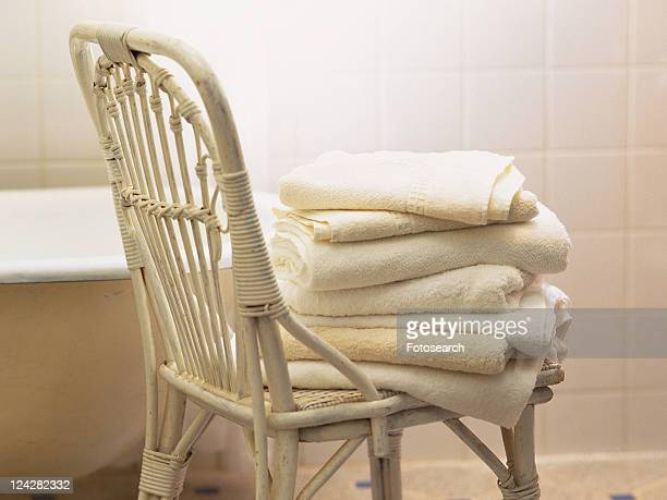 a White Wooden Chair With Several Towels Lying On Top of Each Other, Side View