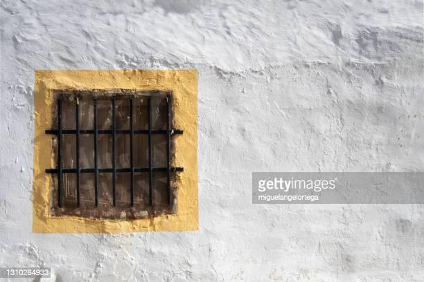 a window protected with bars in a popular dwelling in rural spain - miguelangelortega fotografías e imágenes de stock